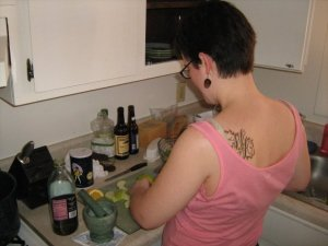 Me cooking with my shoulder tattoo showing: a large capital W and A surrounded by decorative vines.